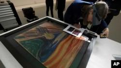 """Avant son départ pour une exposition à la Fondation Louis Vuitton à Paris, le célèbre tableau """"Le Cri"""" d'Edvar Munch est examiné à Oslo le 18 mars 2015."""