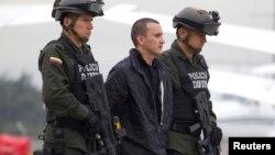 """Alexander Herrera Beltrán, también conocido como """"Rodrigo Pirinolo"""" es escoltado por la policía colombiana antes de su extradición."""