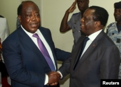 FILE - Charles Konan Banny (L), independent candidate for the 2015 presidential election, shakes hands with Independent Electoral Commission (CEI) President Youssouf Bakayoko (R).