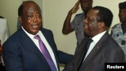 Charles Konan Banny (L), independent candidate for the 2015 presidential election, shakes hands with Independent Electoral Commission (CEI) President Youssouf Bakayoko (R) after registering his candidacy for the presidential election in Abidjan, Ivory Coast, Aug. 21, 2015.