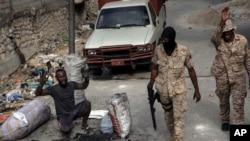 Seorang pria mengangkat tangannya di tengah polisi yang berpatroli di jalanan di pusat kota Port-au-Prince, Haiti, pada 22 September 2021. Warga membuat barikade sebagai bentuk protes terhadap dugaan pembunuhan yang dilakukan polisi pada minggu lalu. (Foto: AP/Rodrigo Abd)