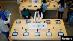 北京三里屯的一家苹果商店里,顾客在看展示出来的苹果手机及其他苹果产品。