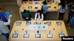 Para capon pembeli mengamati iPhone 5C and 5S di sebuah toko Apple di wilayah Sanlitun, Beijing (30/9). iPhone 6 akan mulai dijual di China dari tanggal 17 Oktober 2014.