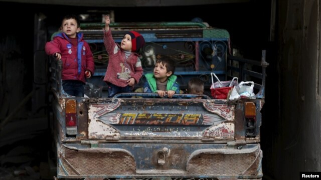 A boy gestures as he sits with others on a pickup truck in the rebel held Douma neighborhood of Damascus, Syria, March 2, 2016.