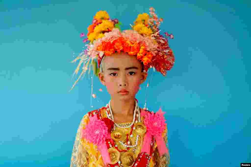 កុមារ Danusorn Sdisaithaworn អាយុ១០ឆ្នាំ ឈរថតរូបក្រោយពេលបានចូលរួមក្នុងពិធីPoy Sang Long ប្រចាំឆ្នាំ ដែលជាពិធីបំបួសជាសង្ឃពុទ្ធសាសនាតាមប្រពៃណី នៅពេលគាត់ទៅលេងផ្ទះសាច់ញាតិរបស់ខ្លួន នៅទីក្រុងMae Hong Son ប្រទេសថៃ។