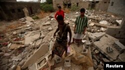 People walk on the wreckage of a house destroyed by an air strike last year that was targeting al Qaeda-linked militants, in the southern Yemeni town of Jaar, February 1, 2013.