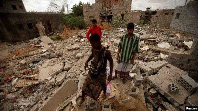 Warga kota Jaar di Yaman melintasi puing-puing bangunan yang terkena serangan udara kelompok militan terkait al-Qaida (1/2). (Reuters/Khaled Abdullah)