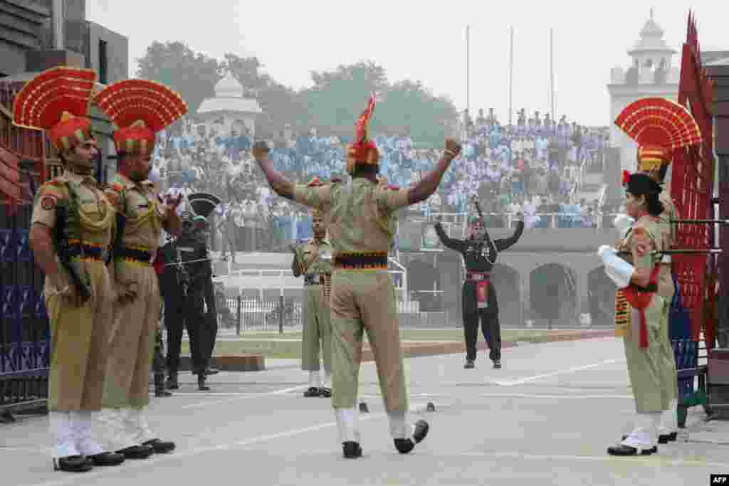 Indian Border Security Force personnel (brown uniforms) and Pakistani rangers (black uniforms) take part in the daily beating of the retreat ceremony, at the India-Pakistan Wagah Border, some 35 kilometers west of Amritsar, Oct, 30, 2017.