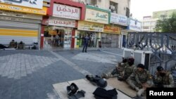 이라크 보안군이 5일 통행금지령이 해제된 뒤 휴식을 취하고 있다.