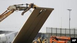 Un prototipo del muro fronterizo cae durante la demolición en la frontera entre Tijuana, México y San Diego, el miércoles 27 de febrero de 2019.