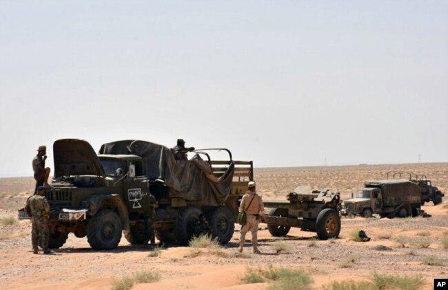 シリアの公式報道機関であるサナ(SANA)が2017年9月3日に発表したこの写真は、シリアのデイル・エル・ズール東部の都市近郊に軍用車両の近くに立っているシリア軍と政治的武装勢力を示している。