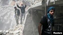 人們在被敘利亞政府軍炸毀的瓦礫堆下尋找生還者。