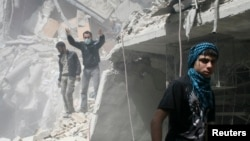 People search for survivors in the rubble of a damaged area that activists said was a result of an airstrike by the Syrian regime, in the Al-Sukkari neighborhood in Aleppo, Syria, April 7, 2013.
