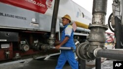 FILE - A worker refuels a truck at a fuel storage depot in Jakarta, Indonesia.