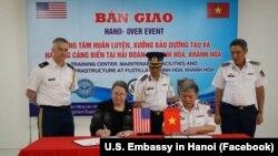 Tổng Lãnh sự Hoa Kỳ Marie Damour (ngồi, bên trái) và Tư lệnh Cảnh Sát Biển Việt Nam Nguyễn Văn Sơn ký biên bản bàn giao dự án vào ngày 9/4/2021.