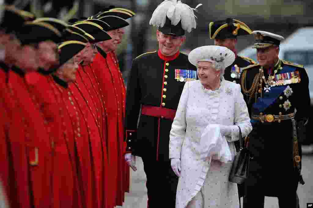 Britain's Queen Elizabeth II, center, and Prince Philip, right, arrive at Chelsea Pier in London, before boarding the royal barge to participate in the Diamond Jubilee River Pageant, June 3, 2012.