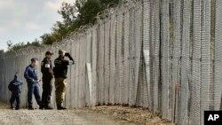 Un policier et un garde-frontière polonais patrouillent avec des policiers hongrois le long de la barrière temporaire à la frontière hongroise-serbe près de Roszke, 180 km au sud-est de Budapest, Hongrie, 13 octobre 2016.