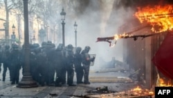 """Las fuerzas de la policía antidisturbios se ubican junto al restaurante """"Le Fouquet's"""" que se quema durante los enfrentamientos con las fuerzas de la policía antidisturbios en los Campos Elíseos en París el 16 de marzo de 2019."""