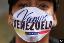 """A Venezuelan migrant wearing a face face mask that reads in Spanish """"Let's go Venezuela"""" walks toward the Venezuelan border after a lockdown ordered by the government, in Bogota, Colombia, Monday, April 6, 2020."""