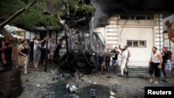 Palestinians inspect a car after it was blown up in Gaza City July 19, 2015.