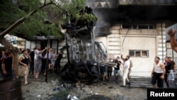 Palestinians inspect a car after it was blown up in Gaza City, July 19, 2015.
