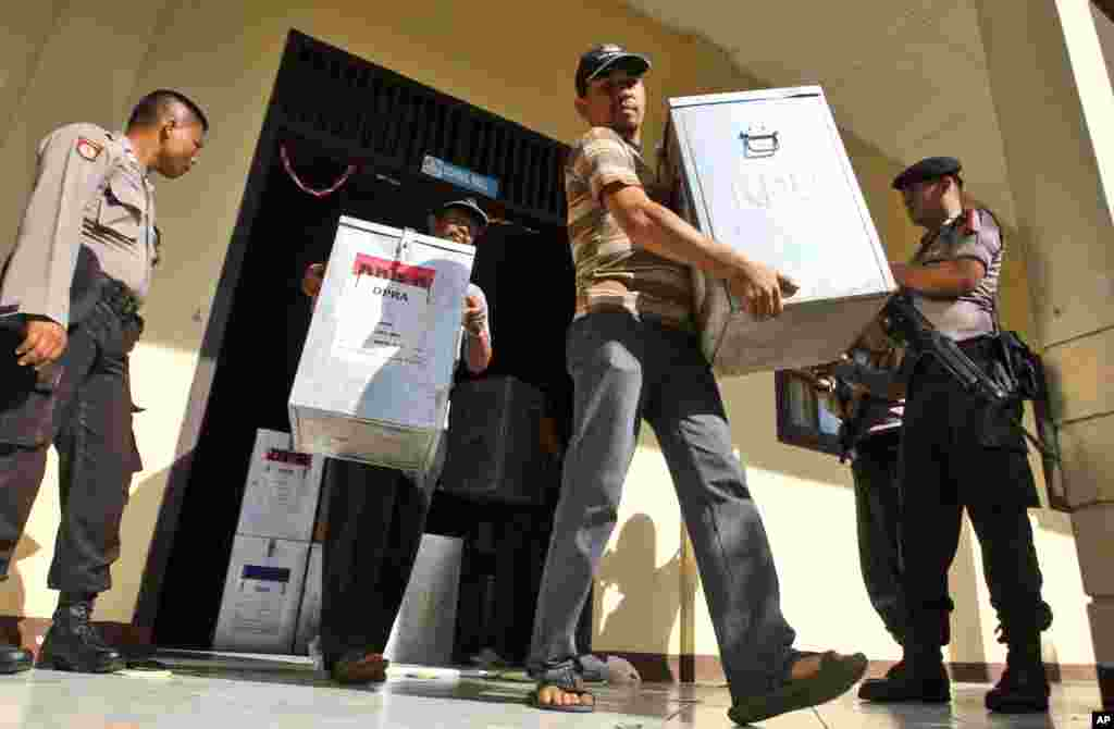Armed police officers stand guard as election officials carry ballot boxes to be distributed to polling stations at a local government office in Banda Aceh, Indonesia, April 8, 2014.