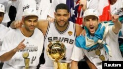 Tony Parker de la France, Tim Duncan, Manu Ginobili de l'Argentine, tous joueurs de San Antonio Spurs posent avec le trophée Larry O'Brien après la victoire des Spurs sur le Heat de Miami à San Antonio, Texas, 15 juin 2014.