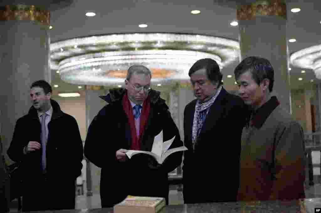 2013年1月9日,谷歌执行董事长施密特与前美国墨西哥州州长理查森在平壤人民大学习堂翻阅一本信息技术教材。