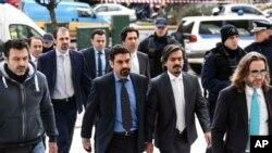 ترک فوجی عہدیدار (درمیان میں) یونانا کی سپریم کورٹ آتے ہوئے۔