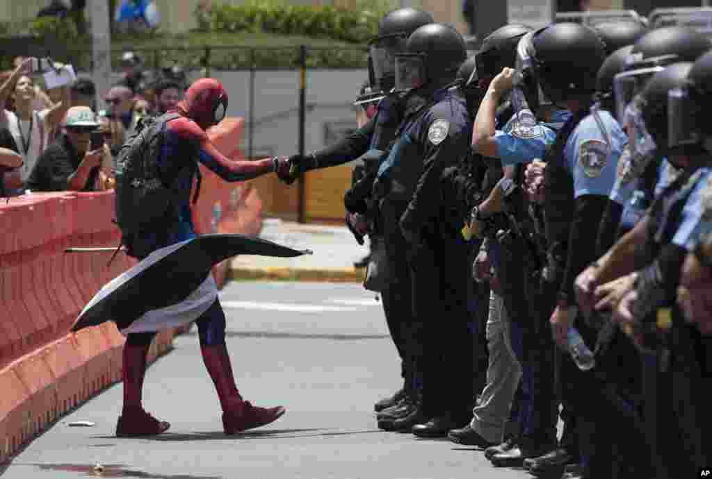 អ្នកតវ៉ាម្នាក់ស្លៀកពាក់ជាបុរសពីងពាង (Spiderman) កំពុងប្រព្រឹត្តការមិនគោរពច្បាប់ នៅពេលលោកឆ្លងចូលទៅក្នុងខ្សែបន្ទាត់ដែលប៉ូលិសបានដាក់ ក្នុងពេលពួកគេតវ៉ាប្រឆាំងនឹងក្រុមប្រឹក្សាសារពើរពន្ធសហព័ន្ធ ដែលជាផ្នែកមួយនៃការប្រារព្ធទិវា «១ឧសភា» នៅទីក្រុងសាំងហ្សង់ ប្រទេសព័រតូរីកូ។