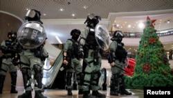 香港防暴警察在一個商場中站在一棵聖誕樹旁面對示威者。 (2019年12月24日)