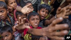 FILE - Rohingya Muslim children, who crossed over from Myanmar into Bangladesh, stretch out their arms out to collect chocolates and milk distributed by Bangladeshi men at Taiy Khali refugee camp, Bangladesh, Sept. 21, 2017.