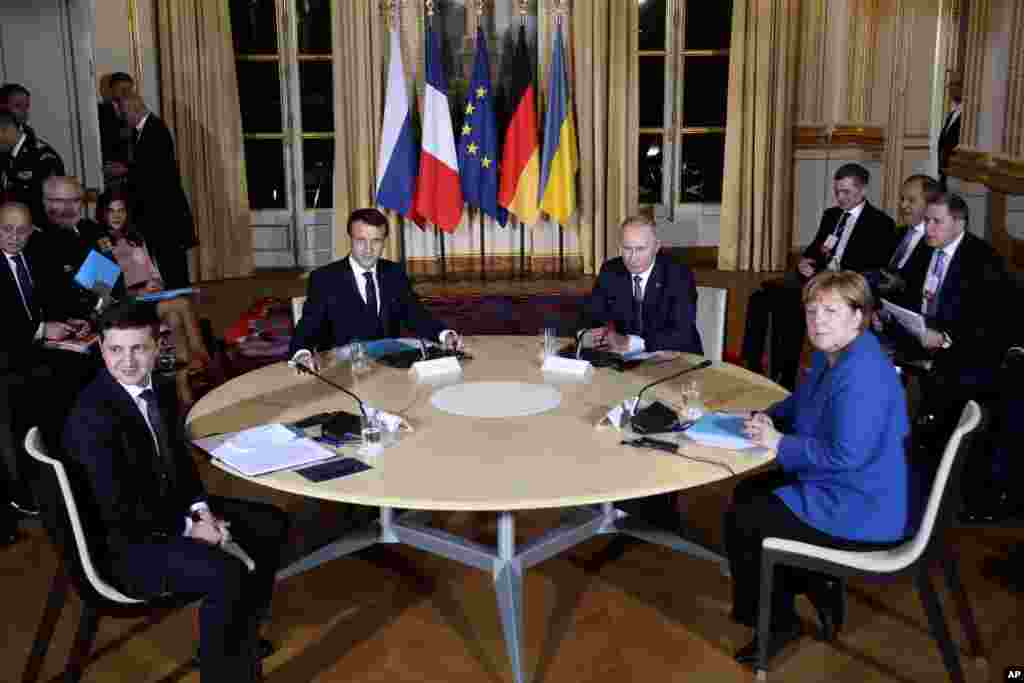 French President Emmanuel Macron, center left, Russian President Vladimir Putin, center right, German Chancellor Angela Merkel and Ukrainian President Volodymyr Zelenskiy, left, attend a working session at the Elysee Palace in Paris, to find a way to end the five years of fighting in eastern Ukraine.