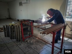 A welder is seen assembling beds at Alfa y Omega migrant shelter in Mexicali, Mexico, in preparation for the Central American caravan's arrival. (R. Taylor/VOA)