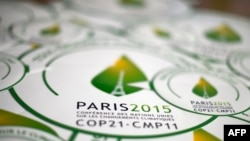 FILE - Stickers with emblem of Climate Change Conference 2015, slated to kick off Nov. 30 in Paris.