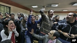 Những người Ai Cập hô khẩu hiệu phản đối nhà cầm quyền quân đội tại phiên xử các nhân viên của các nhóm cổ võ cho dân chủ bị cáo buộc dùng tài trợ của nước ngoài gây tình trạng bất ổn ở Cairo