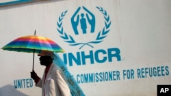 A Congolese man carries an umbrella decorated with a United Nations flag as Muslim and Christian refugees protest together outside the head office of the United Nations refugee agency in Bangui, Central African Republic, Jan. 6, 2014.