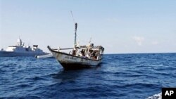 FILE - A handout picture received from The Netherlands Ministry of Defence shows a boat containing alleged Somali pirates being apprehended by Netherlands warship Evertsen.
