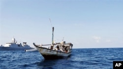 A handout picture received from The Netherlands Ministry of Defence shows a boat containing alleged Somali pirates being apprehended by Netherlands warship Evertsen acting as part of EU counter piracy operations at sea some 150 nautical miles off the coas