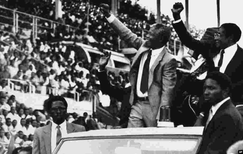 Le vice-président de l'ANC Nelson Mandela, au centre, et le président du Zimbabwe, Robert Mugabe, à droite, saluent la foule au Zimbabwe, pour Mandela Day, le 5 mars 1990, à Harare, Zimbabwe.