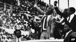 Nelson Mandela, l'ancien président d'Afrique du Sud, au centre, et Robert Mugabe, l'ancien président du Zimbabwe, à droite, saluent la foule pour Mandela Day à Harare, au Zimbabwe, le 5 mars 1990.