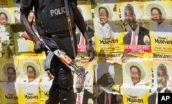 FILE - An armed Ugandan riot policeman patrols past campaign posters for long-time President Yoweri Museveni, as well as local members of Parliament, on a street in Kampala, Uganda, Feb. 17, 2016.