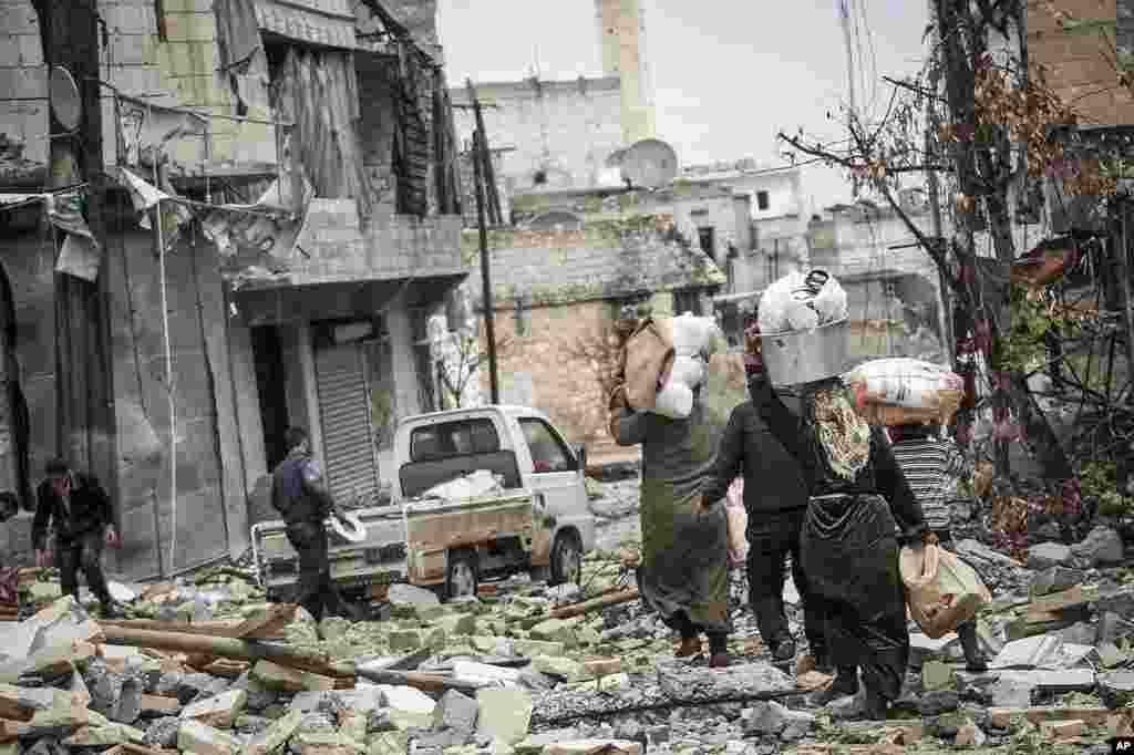 Syrian residents carry their belongings after their homes were damaged due to fighting between Free Syrian Army fighters and government forces in Aleppo, Syria, December 11, 2012.