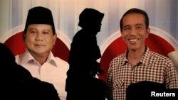 Seorang perempuan melewati poster Prabowo Subianto (kiri) dan Joko Widodo pada acara Debat Capres di Jakarta tahun 2014 (foto: ilustrasi).