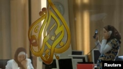 FILE - The Al Jazeera logo is seen through a window at the offices of the Arabic news channel in Ramallah, West Bank.
