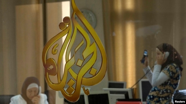 FILE - The Al-Jazeera logo is seen through a window at the offices of the Arabic news channel in Ramallah, West Bank, July 15, 2009.