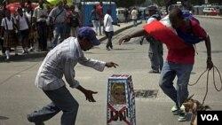 Demonstran di Port-au-Prince, Haiti, menari-nari di sekeliling peti mati palsu yang diberi lambang PBB dalam protes menentang PBB terkait merebaknya kolera di negara itu,