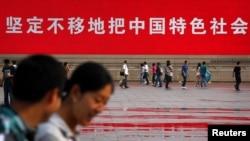 Warga melintas di depan slogan propaganda dalam peringatan 23 tahun tragedi di Lapangan Tiananmen, Beijing(3/6).
