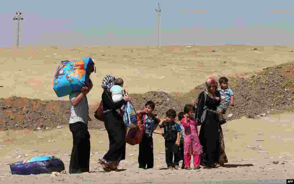 Displaced people, who have fled violence in Iraq's northern Nineveh province, carry their belongings as they arrive in al-Hamdaniyah, 76 kms west of the Kurdish autonomous region's capital, Arbil.