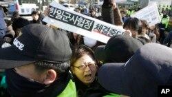 Seorang demonstran bentrok dengan polisi dalam aksi unjuk rasa menentang perjanjian pertukaran informasi intgelijen (GSOMIA) antara Korea Selatan dan Jepang di sepan kantor Menteri Pertahanan Korea Selatan di Seoul, 23 November 2016 (AP Photo/Ahn Young-joon).